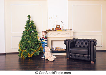 Child boy playing with soft toy bear near the Christmas tree.