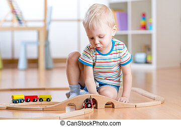 Child boy playing with wooden railway on the floor