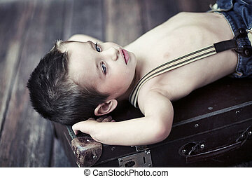 Child boy relaxing on the suitcase