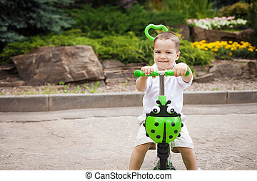 child boy riding a trike in the park