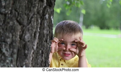 Child boy shows up from behind tree and fooling around,...