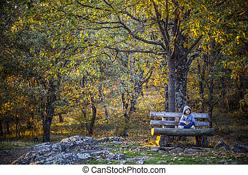 Child boy sitting in the middle of the forest, Extremadura, Spain