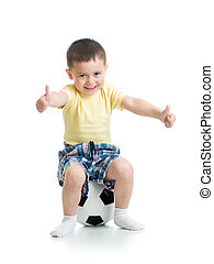 Child boy sitting on soccer ball with thumbs up sign.