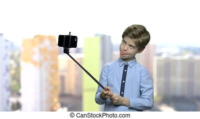 Child boy sticking out tongue while taking selfie. Preteen...