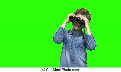 Child boy tourist looking through binoculars. Green hromakey...