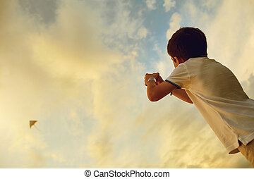 Child boy with a kite in the sky with clouds.