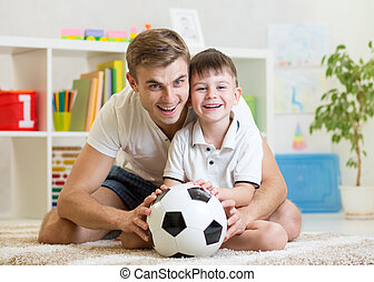 child boy with dad play football at home
