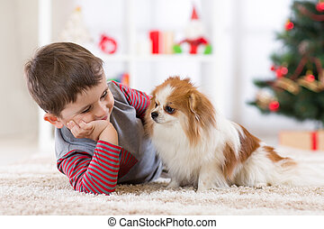 Child boy with dog lying at christmas tree on the floor.