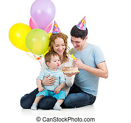child boy with parents celebrating birthday and blowing candles on cake