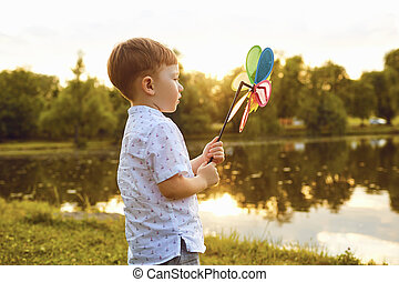 Child boy with toy in hand at sunset in park.