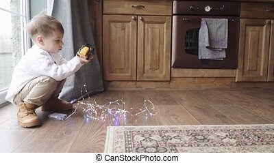 Child boy playing with tractor on kitchen floor