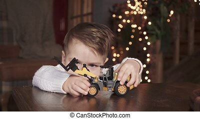 Child boy with a gift and a toy tractor near the new year tree