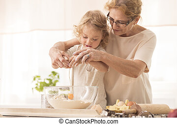 Child breaking the egg into a bowl - Senior nanny helping...