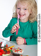 Child brushing teeth after snacking