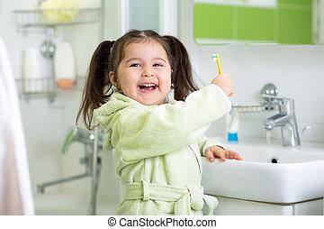 Child brushing teeth in bathroom