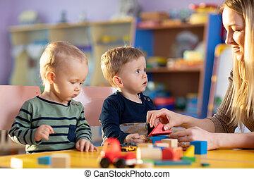 Child building blocks with a teacher in the nursery