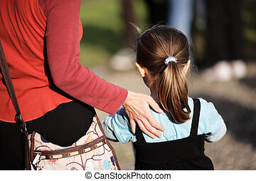 Mother and daughter with hand on shoulder are going away