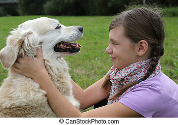 Child caressing dog on a meadow