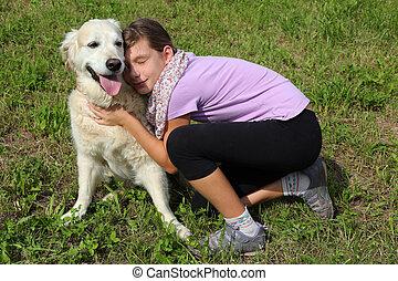 Child caressing her pet dog