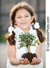 child caring for the invironment (focus on tree)