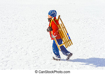 child carries his sledge up the hill in wintertime