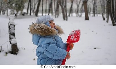 child catches snowflakes mouth in slowmotion