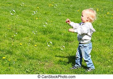 Child catching soap bubbles