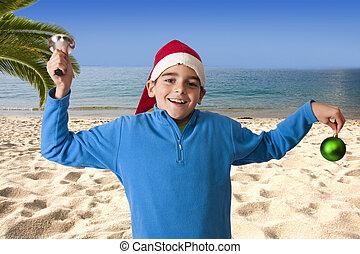 child celebrating christmas on the beach