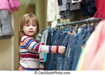 child  chooses jeans at shop