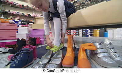 Child choosing and trying on new shoes for girls in children shoe store