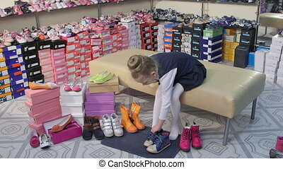 Child choosing and trying on new shoes for junior girls in children shoe store