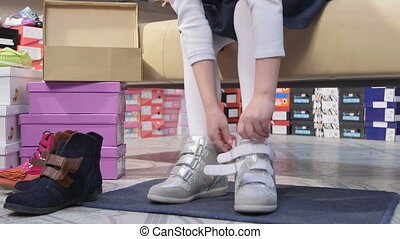 Child choosing footwear in childrens shoe store tries on new...