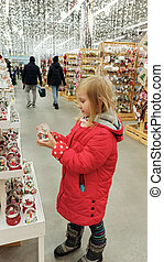 Child choosing glass sphere with artificial snow. Christmas decorations in shop