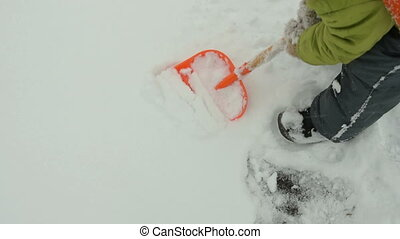 Child cleaning snow with toy shovel