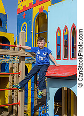 Child climbing down little house at playground