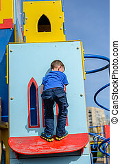 Child climbing into little house at playground