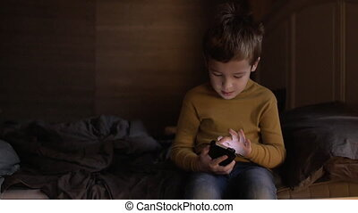 Child controlling cellphone with voice - Boy sitting on...
