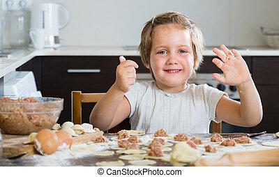 Child cooking meat dumplings - Smiling little girl making...