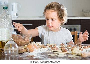 Child cooking meat dumplings - Happy child cooking meat...