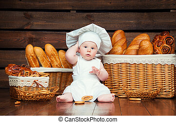 Child cooks eating a bagel on the background of baskets with rolls and bread.