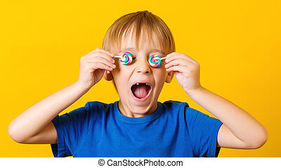 Child covered eyes with lolipops. Cute excited boy over yellow background.