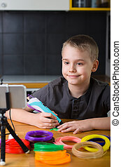 Child creating with 3d printing pen. Happy boy does something with colored ABS plastic and using online lesson.