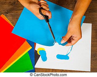 child cuts out of paper sheets of colored paper kids art crafts concept - Color Paper For Kids