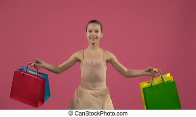 Child dancer in costume bounces on the spot with shopping...