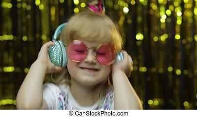 Child dances, listens music on headphones. Little kid girl dancing, having fun, relaxing, enjoying