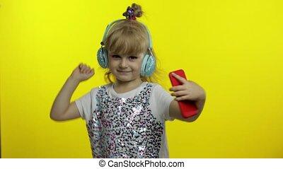 Child dances with smartphone, listening to music on headphones. Little kid girl dancing, having fun