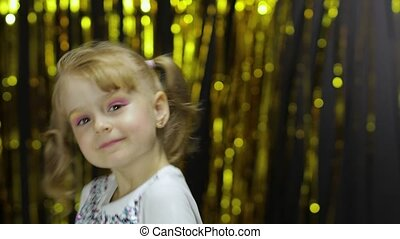 Child dancing, enjoying music, moving in dynamic winning dance. Little fun blonde kid teen teenager girl 4-5 years old in shiny white t-shirt posing isolated on foil fringe golden curtain background