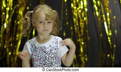 Child dancing, enjoying music, moving in slow rhythm dance. Little fun blonde kid teen teenager girl 4-5 years old in shiny white t-shirt posing isolated on foil fringe golden curtain background