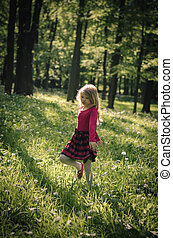child dancing in forest