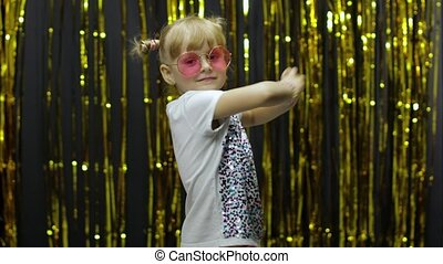 Stylish child dancing, pointing fingers at camera. Little fun blonde kid teen teenager girl 4-5 years old in pink sunglasses posing isolated on background with foil fringe golden curtain in studio